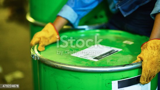 Human hands in protective gloves holding oil drum