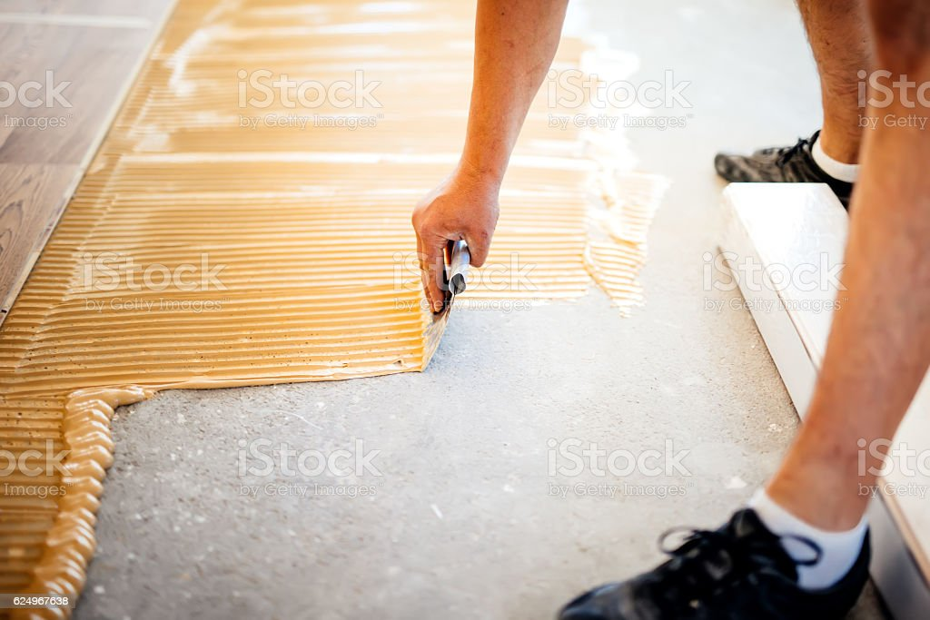 worker adding glue on floor, preparing surface for wood parquet stock photo