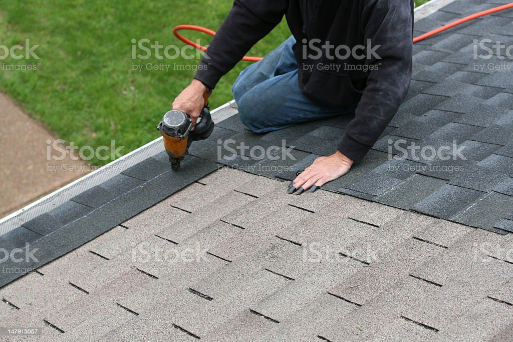 Worker adding shingles to roof stock photo