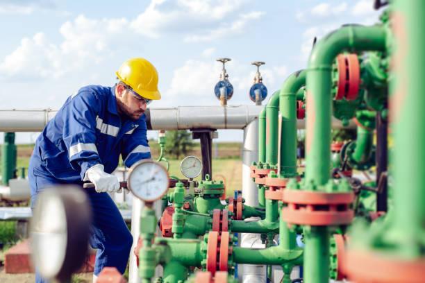 arbeiter einstellen zu messen, bei öl-raffinerie - luftventil stock-fotos und bilder