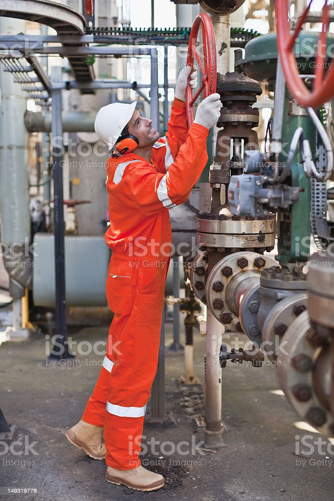 Worker adjusting gauge at oil refinery stock photo