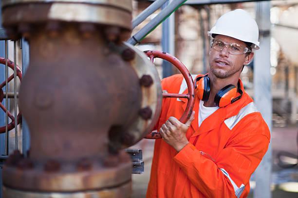 arbeiter anpassen gauge in ölraffinerie - luftventil stock-fotos und bilder