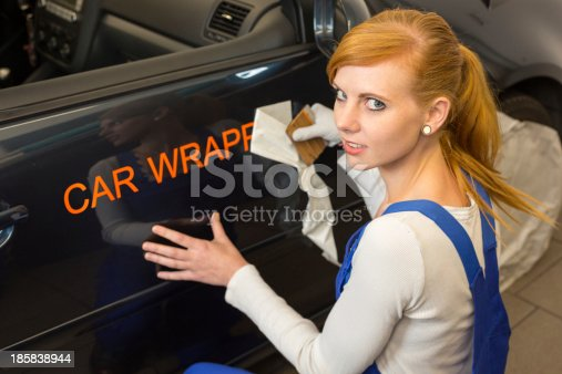 istock Worker affixes car wrapping foil for advertisement on vehicle 185838944