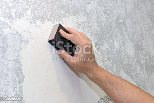 image of worker aligns the sandpaper wall