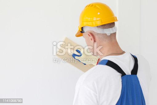 Worker aligns with sandpaper finishing surface
