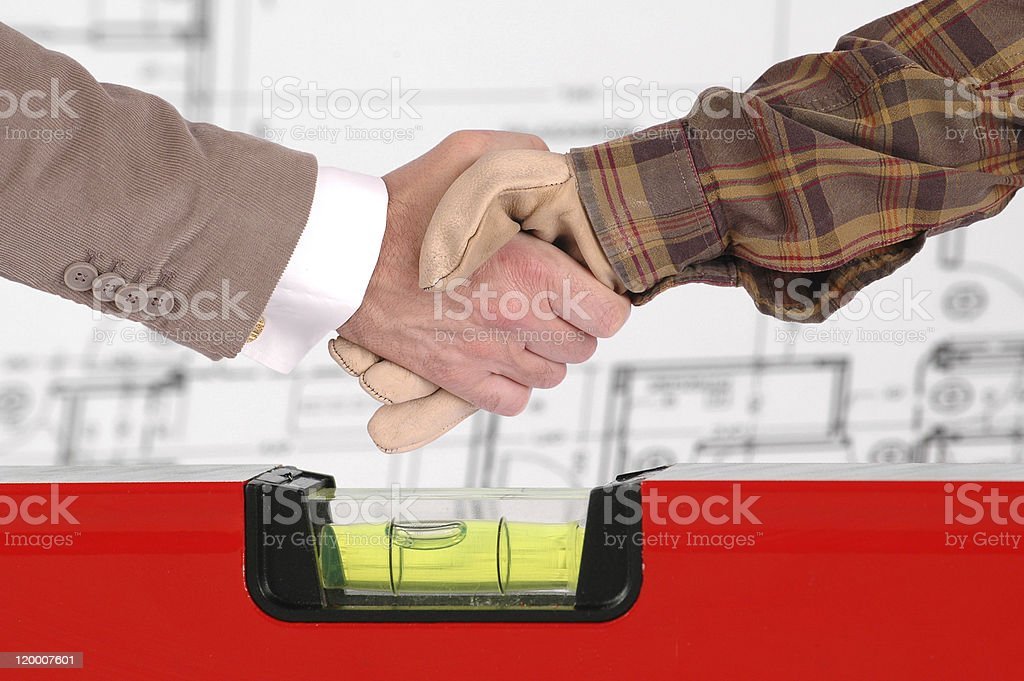 Worker and a businessman shaking hands over house renovation plans royalty-free stock photo