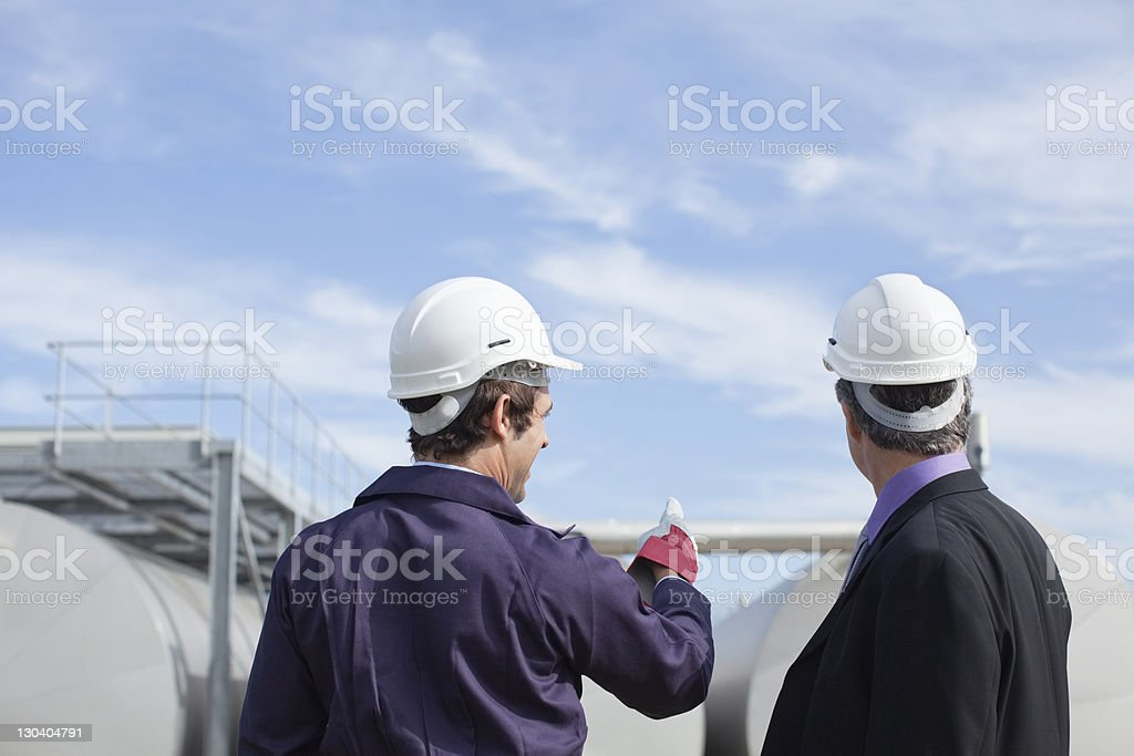 Worker and businessman examining tanks outdoors stock photo