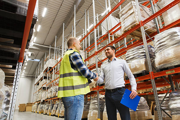 worker and businessmen with clipboard at warehouse stock photo