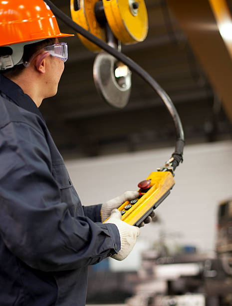 Worker and crane hook Worker holding crane hook button working in factory with safety workwear overhead projector stock pictures, royalty-free photos & images