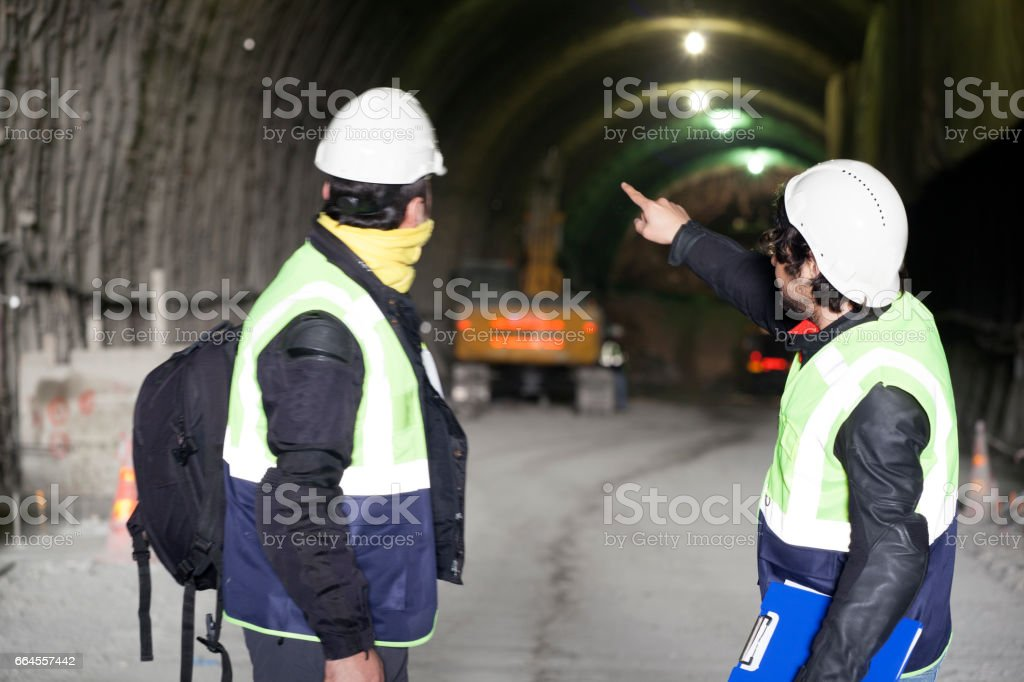 Worker and engineer working in tunnel construction site royalty-free stock photo