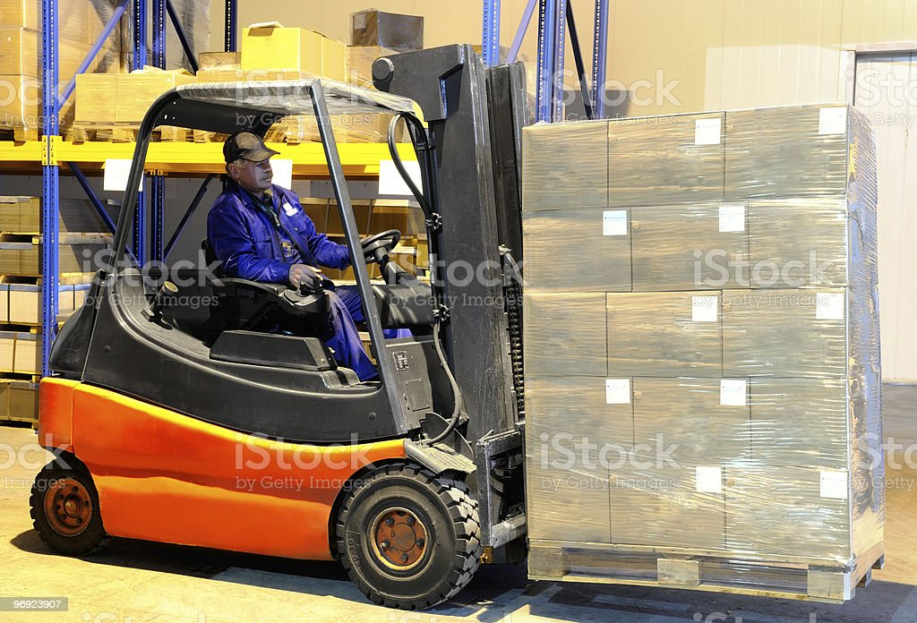 worker and forklift loader at warehouse royalty-free stock photo