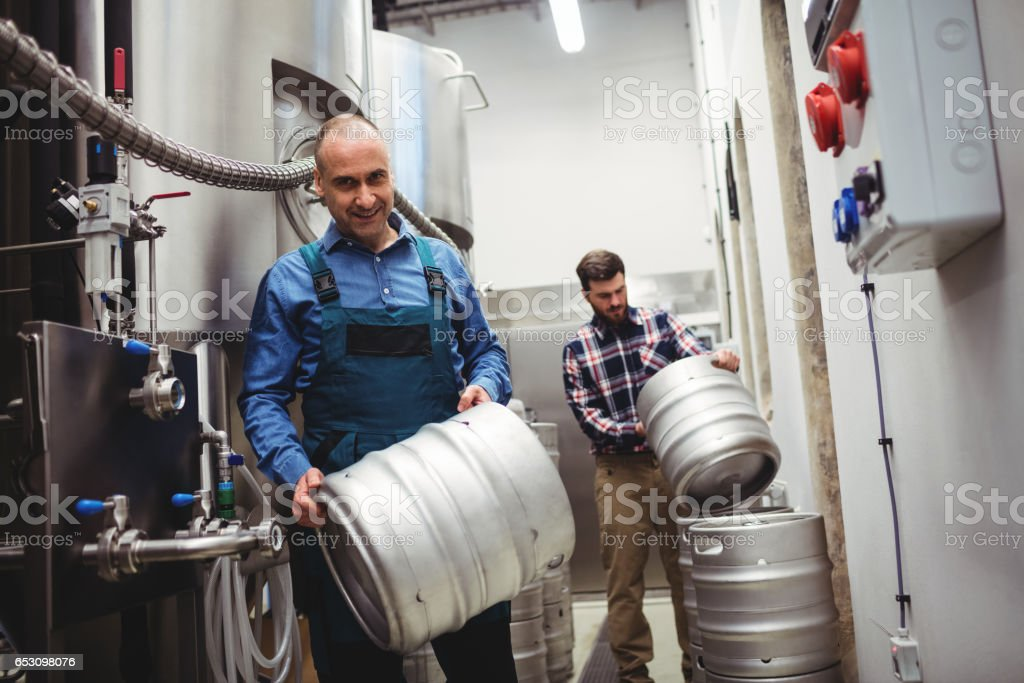 Worker and manufacturer carrying kegs stock photo