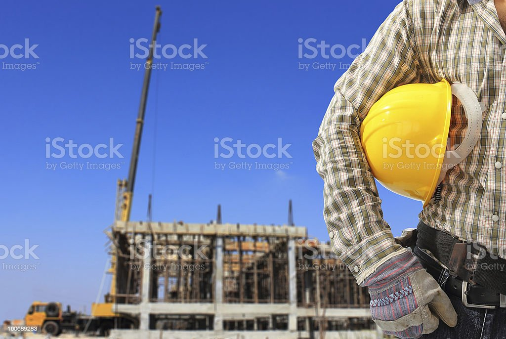 Worker and the blurred construction against blue sky Worker and the blurred construction against blue sky Blue Stock Photo