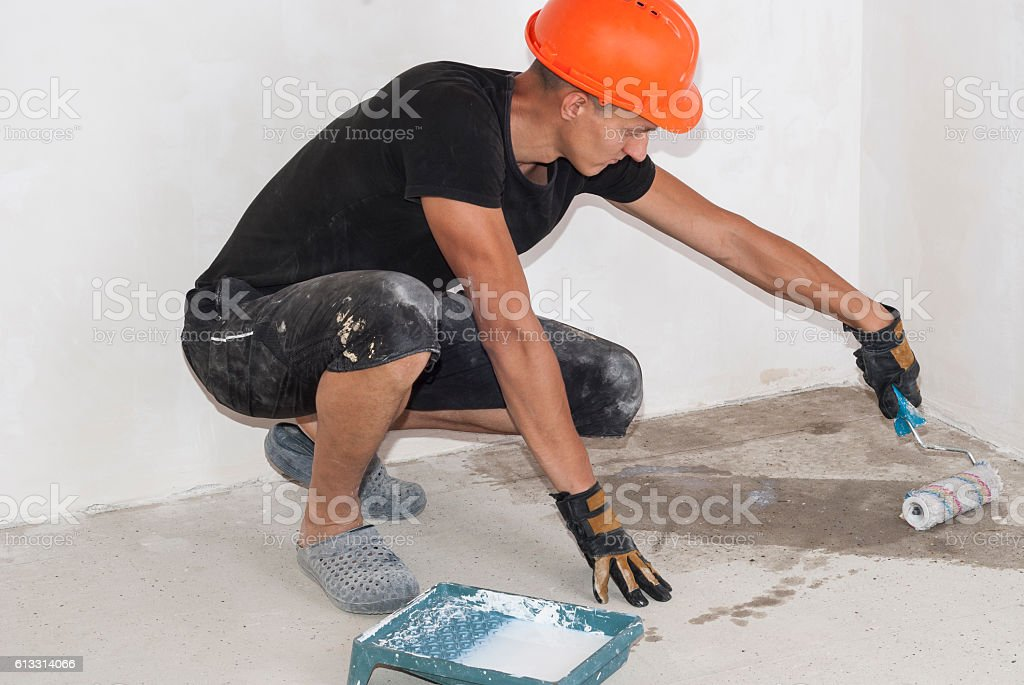 Worker applies primer on the floor stock photo