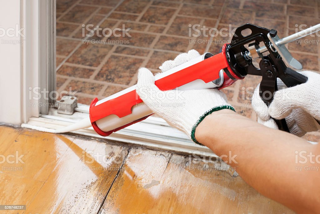 Worker applies silicone caulk on the wooden floor stock photo