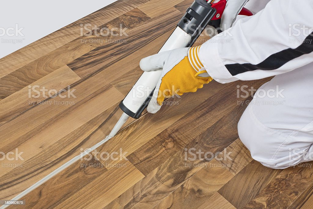 worker applies silicone sealant spaces of old wooden floor stock photo