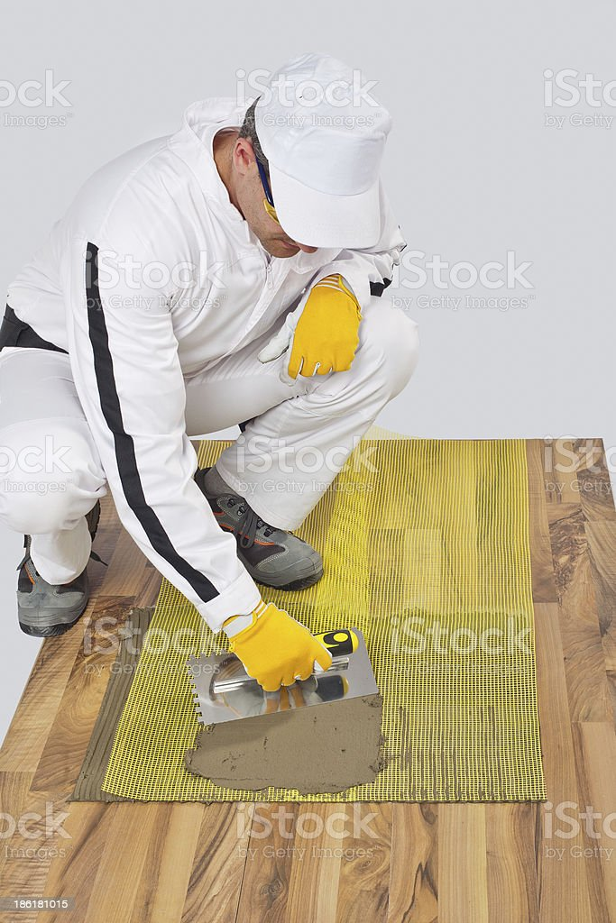 Worker applies tile adhesive with reinforcement mesh stock photo