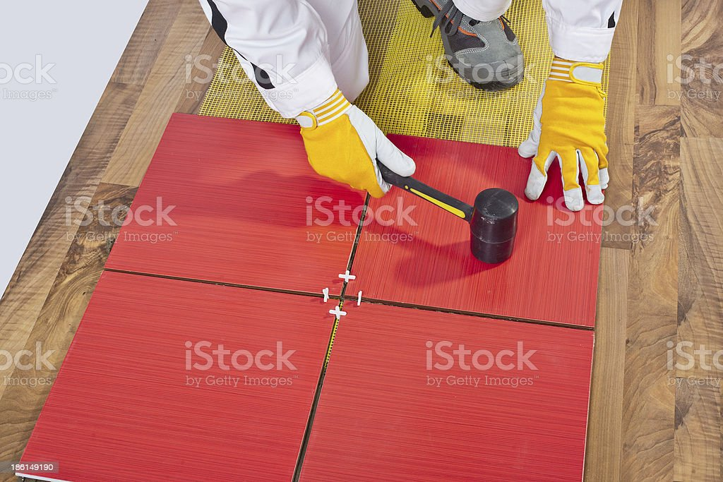 Worker Applies with Rubber Hummer Tile on a wooden Floor stock photo