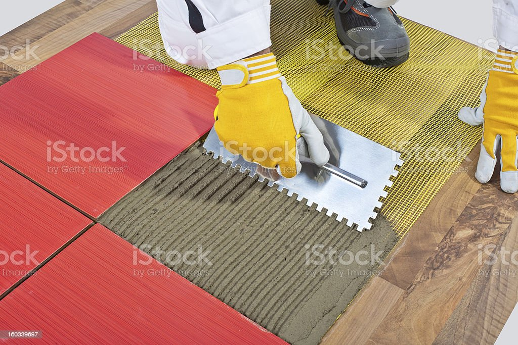 worker apply ceramic tiles on wooden floor mesh trowel royalty-free stock photo