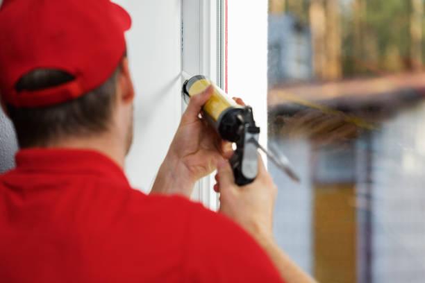worker applying caulk around window frame stock photo