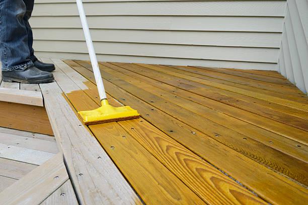 worker applying stain to deck - houtbeits stockfoto's en -beelden