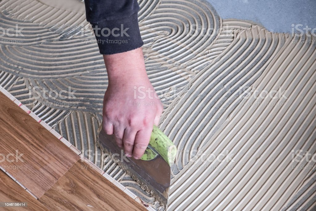 Worker applying wooden flooring adhesive stock photo