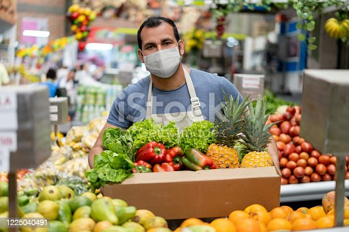 Latin American worker at a food market restocking the shelves and wearing a facemask while holding a box with fruits and vegetables - pandemic lifestyle concepts