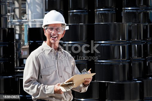 Senior man, 60s, working at chemical plant, standing by steel drums with clipboard