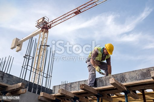 istock Worker At Construction Site Is Fixing The Form For The Beam 897664288