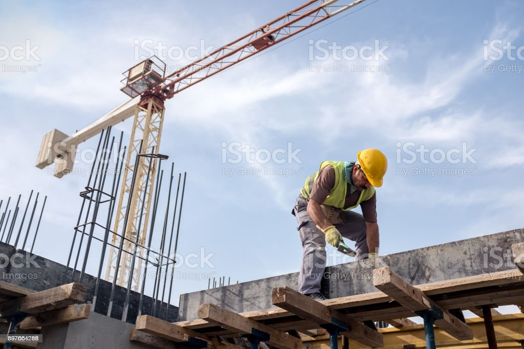 Worker At Construction Site Is Fixing The Form For The Beam - foto stock