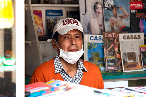 Worker at kiosk wearing a mask amid coronavirus outbreak Worker at kiosk wearing a mask amid coronavirus outbreak in south America. Magazines in the background. amid stock pictures, royalty-free photos & images