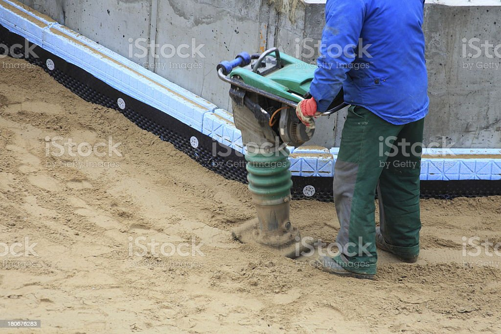 Worker at site working with compress tool royalty-free stock photo