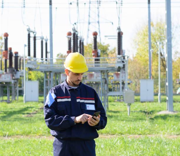 Arbeiter am Stromumspannwerk. Mit Smartphone. – Foto