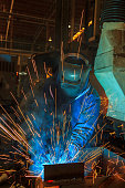 istock Worker at the factory is welding assembly automotive part 990681202