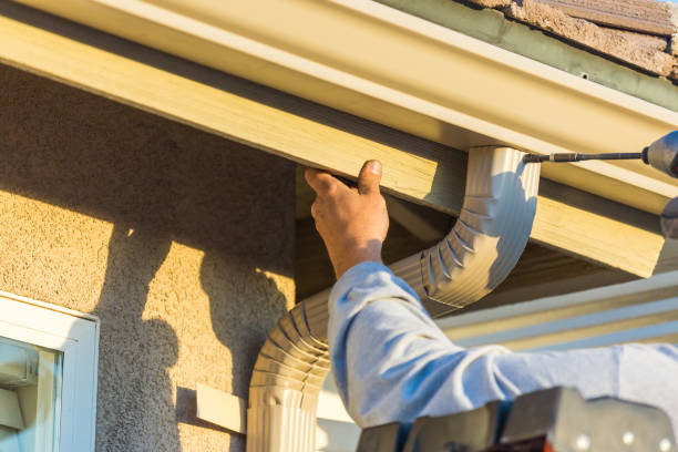 Worker Attaching Aluminum Rain Gutter to Fascia of House. stock photo