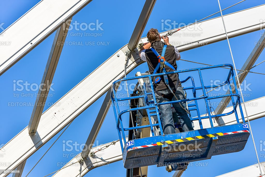 worker attaching fasteners to a beam stock photo