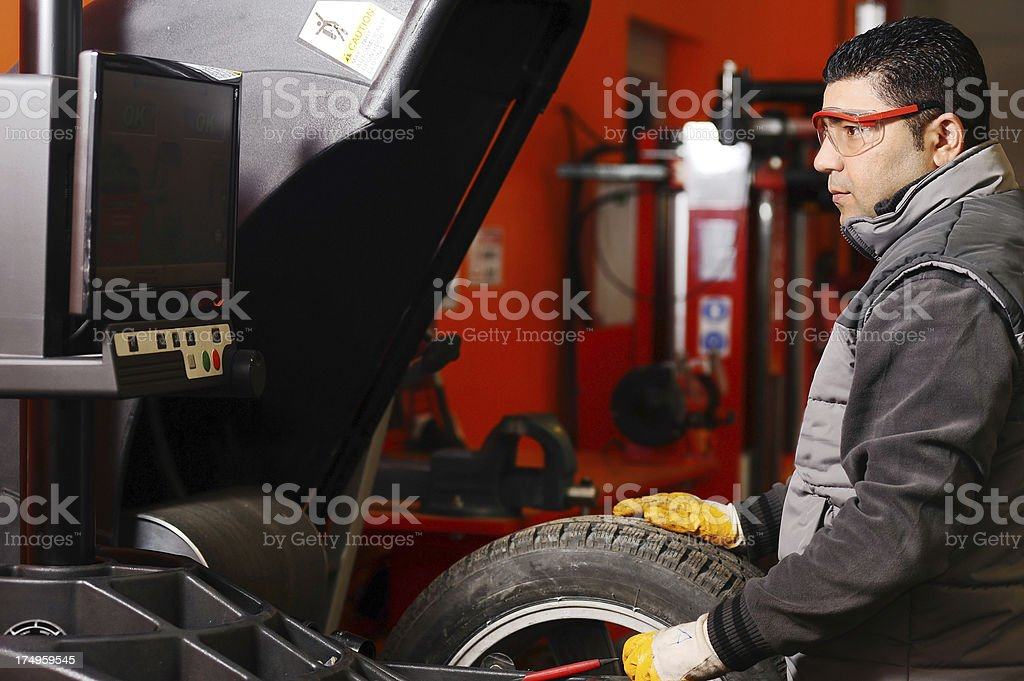 Worker balancing car wheel stock photo