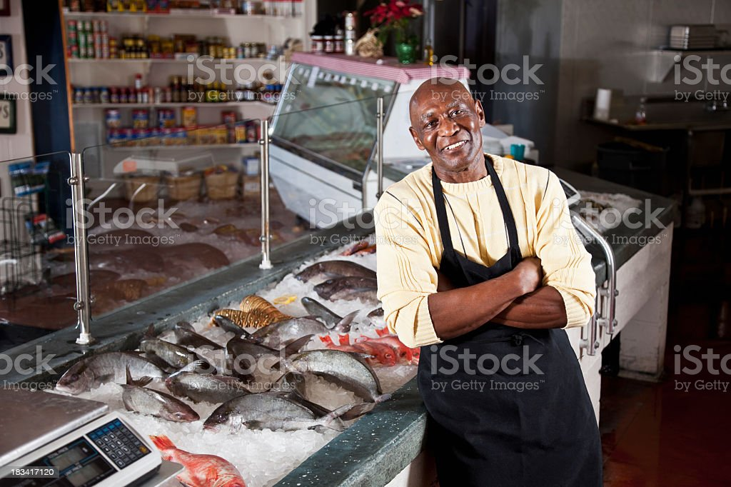 Worker behind counter in fish market royalty-free stock photo