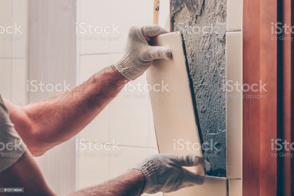 Worker breaks the remnants of tiles off the wall stock photo