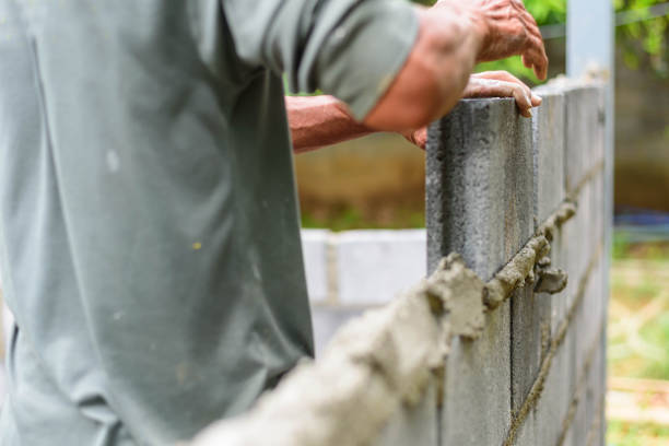 Worker brick the cement wall in construction site stock photo