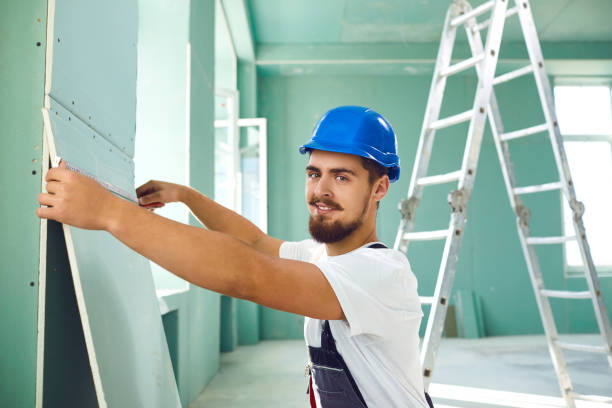 Worker builder installs plasterboard drywall at a construction stock photo