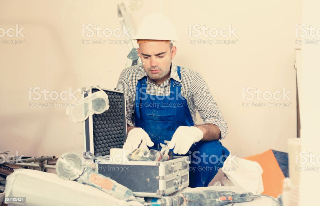 Worker builder searching tools for repair royalty-free stock photo