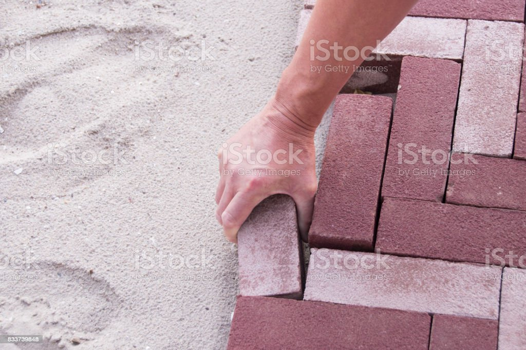worker building a street with red bricks stock photo