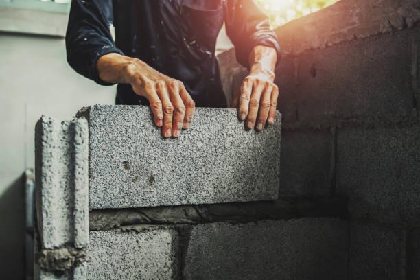 Arbeiter bauen Wandsteine mit Zement – Foto