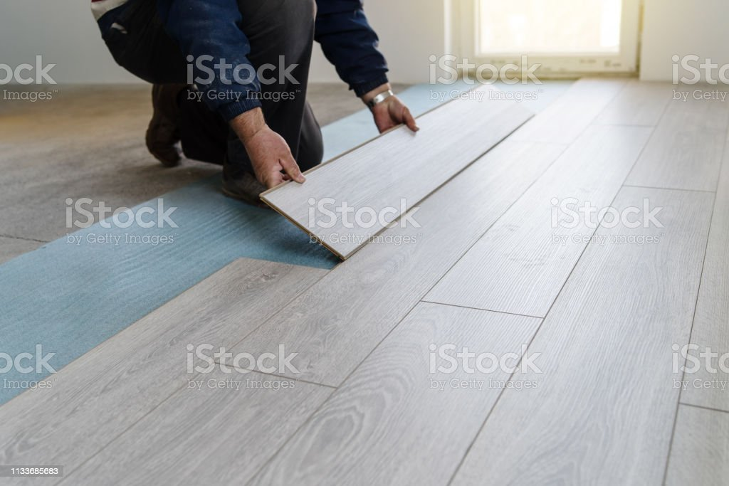 Worker carpenter doing laminate floor work Worker carpenter doing laminate floor work Adjusting Stock Photo