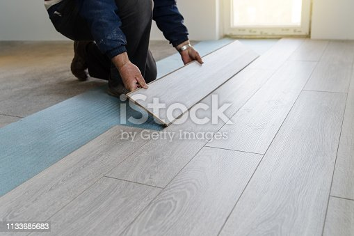 istock Worker carpenter doing laminate floor work 1133685683