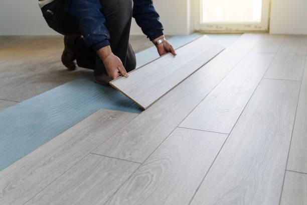 worker carpenter doing laminate floor work - pavimento foto e immagini stock