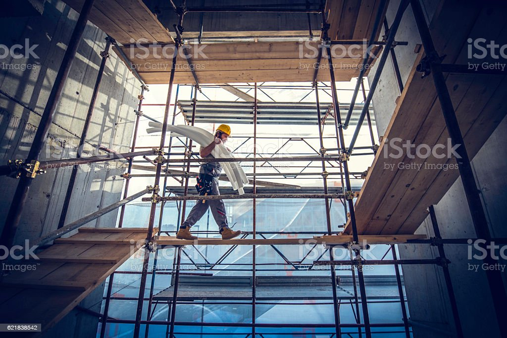 Worker carrying pipes stock photo