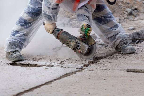 worker catching and using electric cutting machine tool to cut concrete floor with dirty dust spreading in air, worker catching and using electric cutting machine tool to cut concrete floor with dirty dust spreading in air, grinding stock pictures, royalty-free photos & images