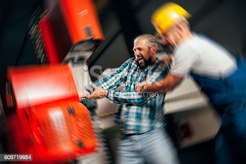 istock Worker caught in the machine and seriously injured 609719684